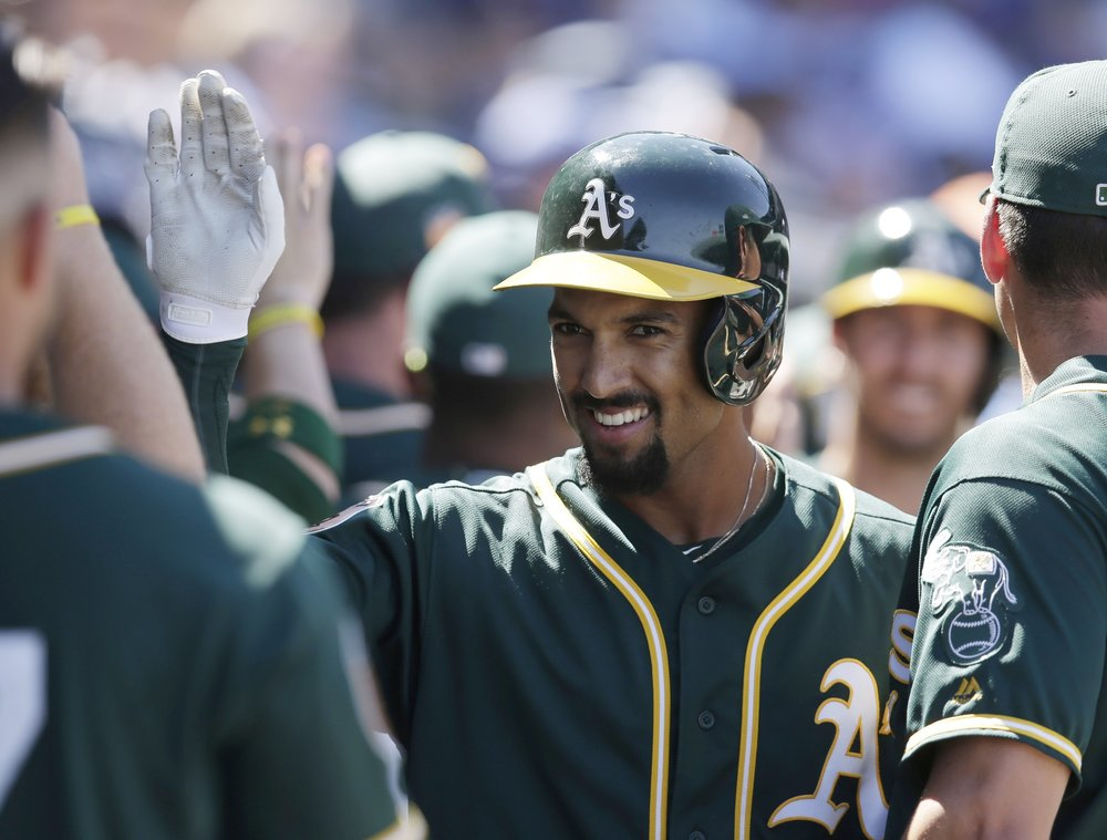 Marcus Semien high fives his teammates after hitting a home run.