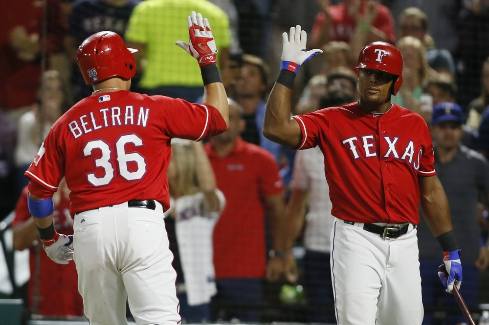 Carlos Beltran and Adrian Beltre exchange a high five.