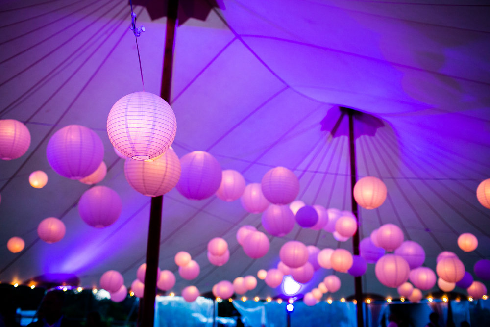"Strands of cafe lights 30"" apart with varying sizes of white even-ribbed paper lanterns.  Image by  Mark Davidson Photography ."