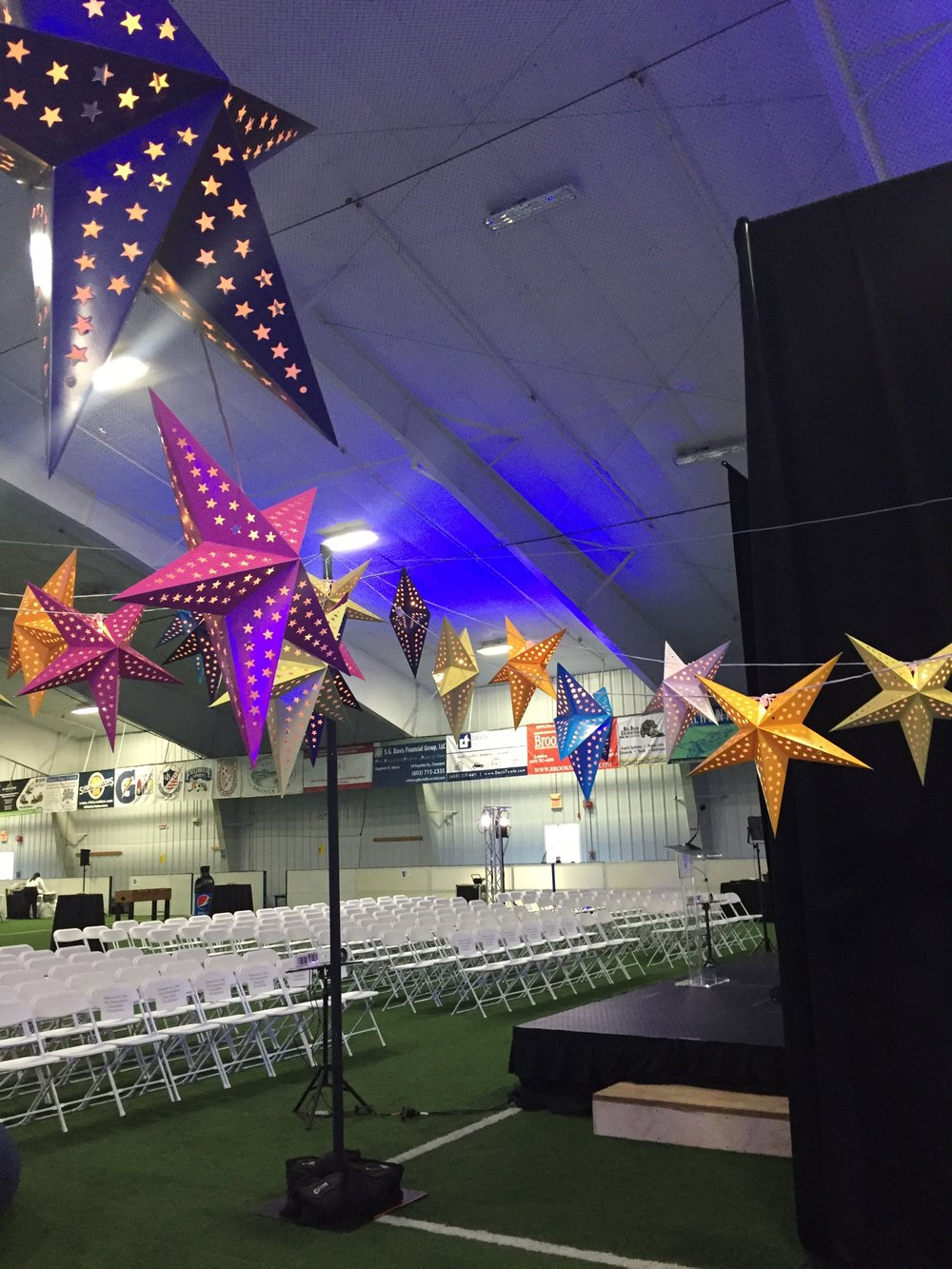Star lanterns on cafe light strands installed with heavy bases and upright poles in a sports arena, Fieldhouse Sports, Bow, NH.