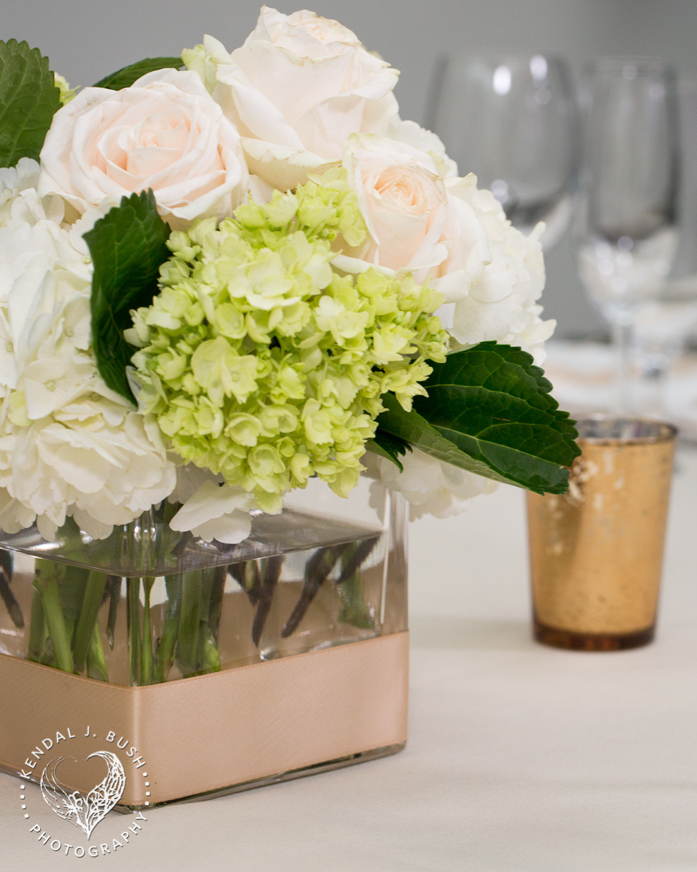 White hydrangea studded with cream vendela roses and mini green hydrangea.  The vase is wrapped in a gold satin ribbon.  Image by Kendal J. Bush Photography.