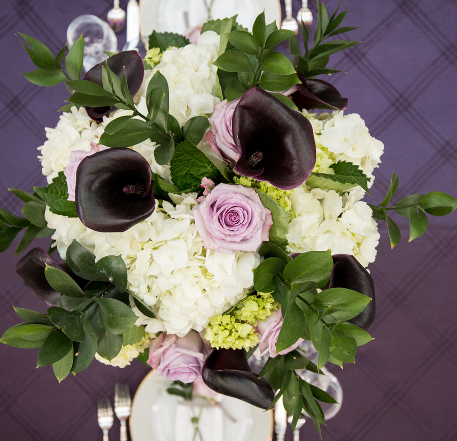 A tall centerpiece of white hydrangea, mini green hydrangea, purple roses, dark purple calla liles, and italian ruskus. Image by Kendal J. Bush Photography.