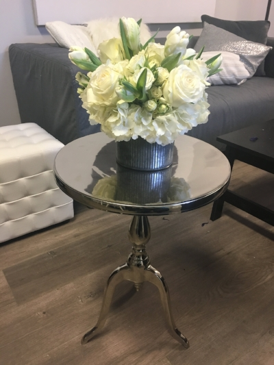 Chrome round accent table with flared legs.