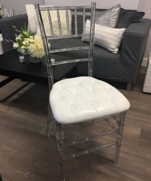 Clear acrylic chiavari chair with white tufted cushion.