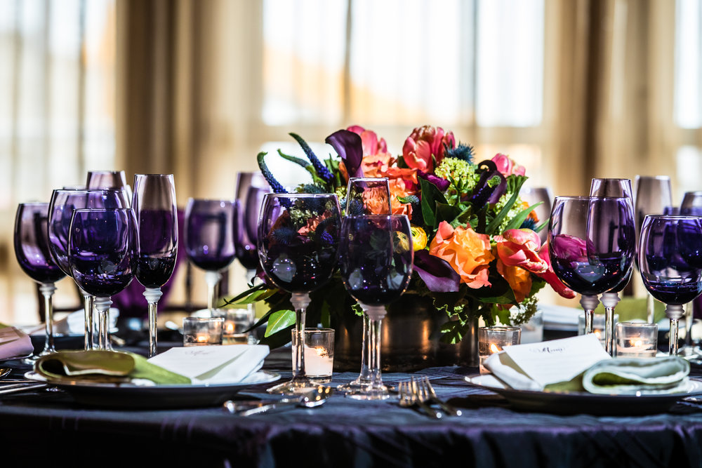 Fall on the ocean.  Reception table featuring eggplant linens, green, orange and eggplant florals, and upgraded linens, china, glassware and flatware.  Image by Eric McCallister Photography.