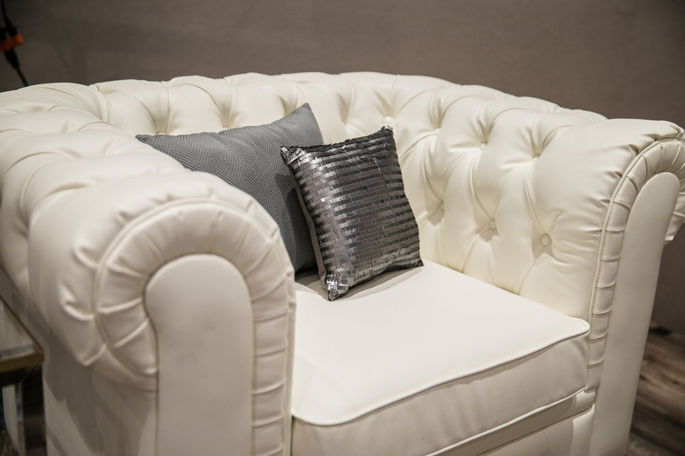 White tufted leather chairs with dark wooden feet.