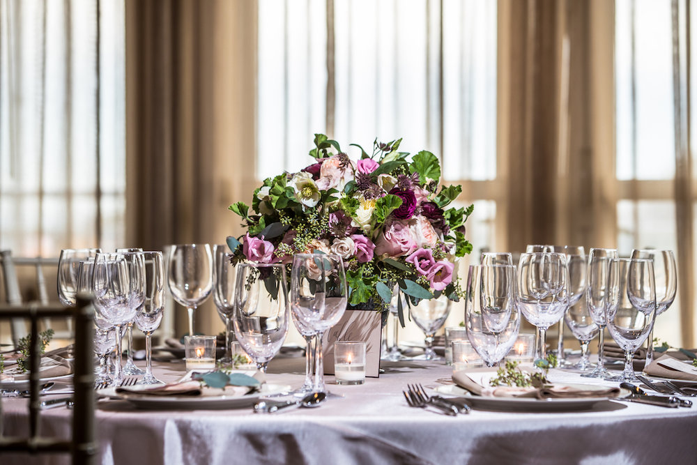 Romantic wedding floral centerpiece at Inn by the Sea in Cape Elizabeth, Maine.  Image by Eric McCallister Photography.