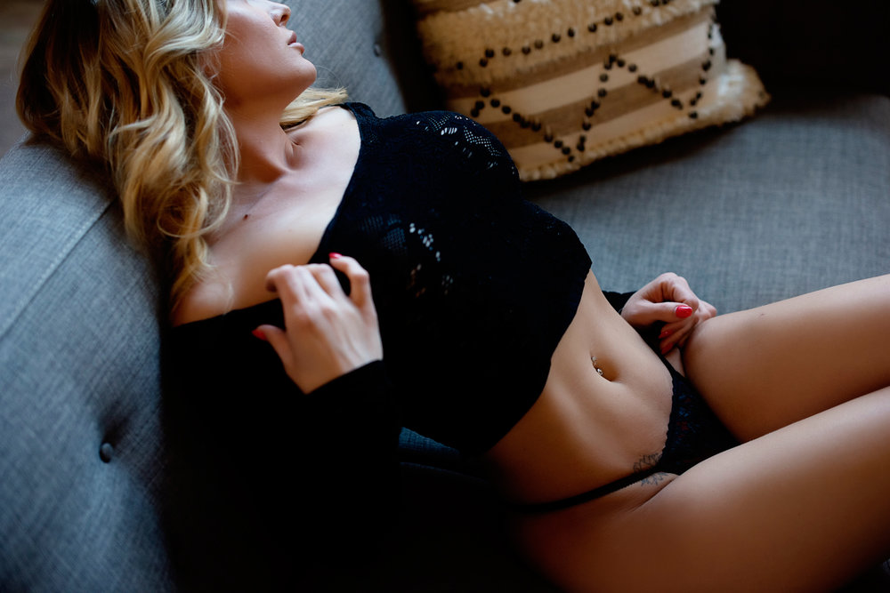 woman posing in lingerie for boudoir photographer on couch