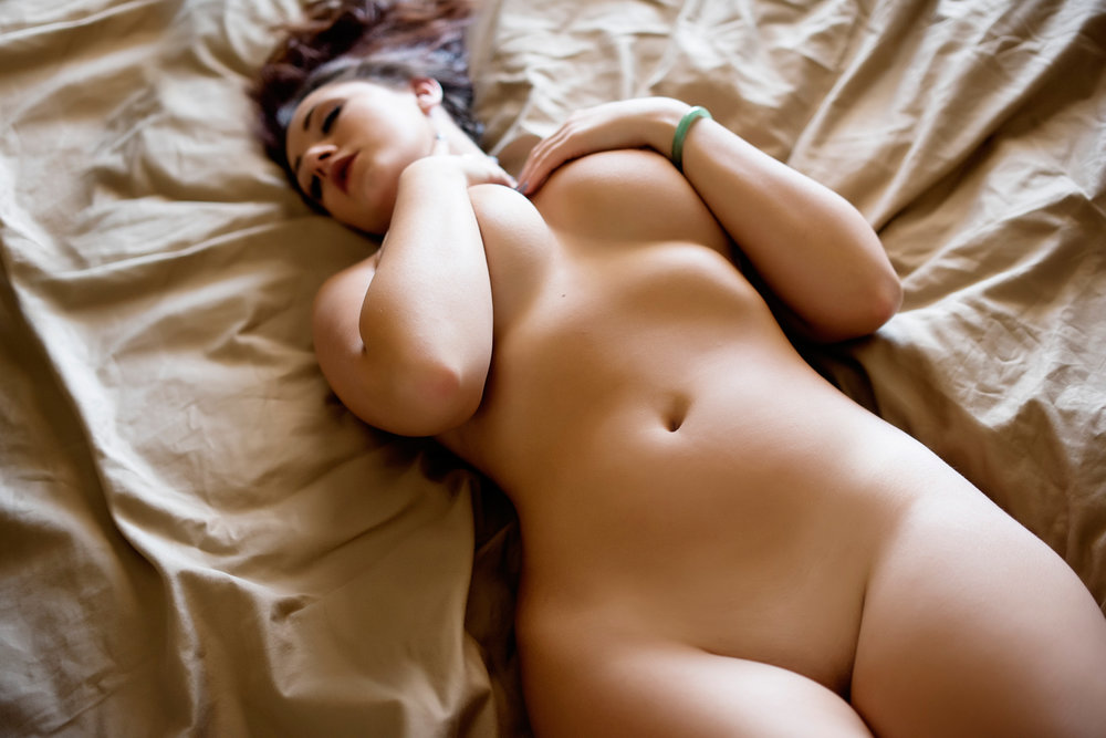 artistic nude photo of female model on bed