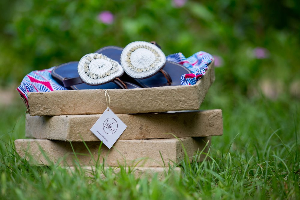 Wazi Shoe boxes made from recycled cardboard and dry in the sun of AfriCraft's courtyard in Dar es Salaam.