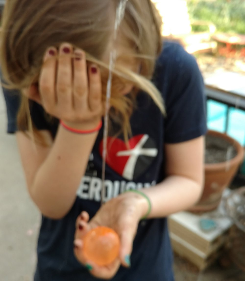 An eyeful of water after piercing the water balloon with a pin.
