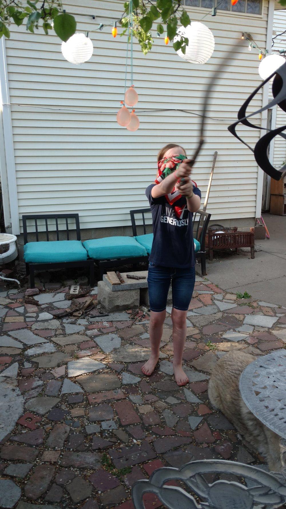 Olivia takes a turn swinging at the water balloon pinata.