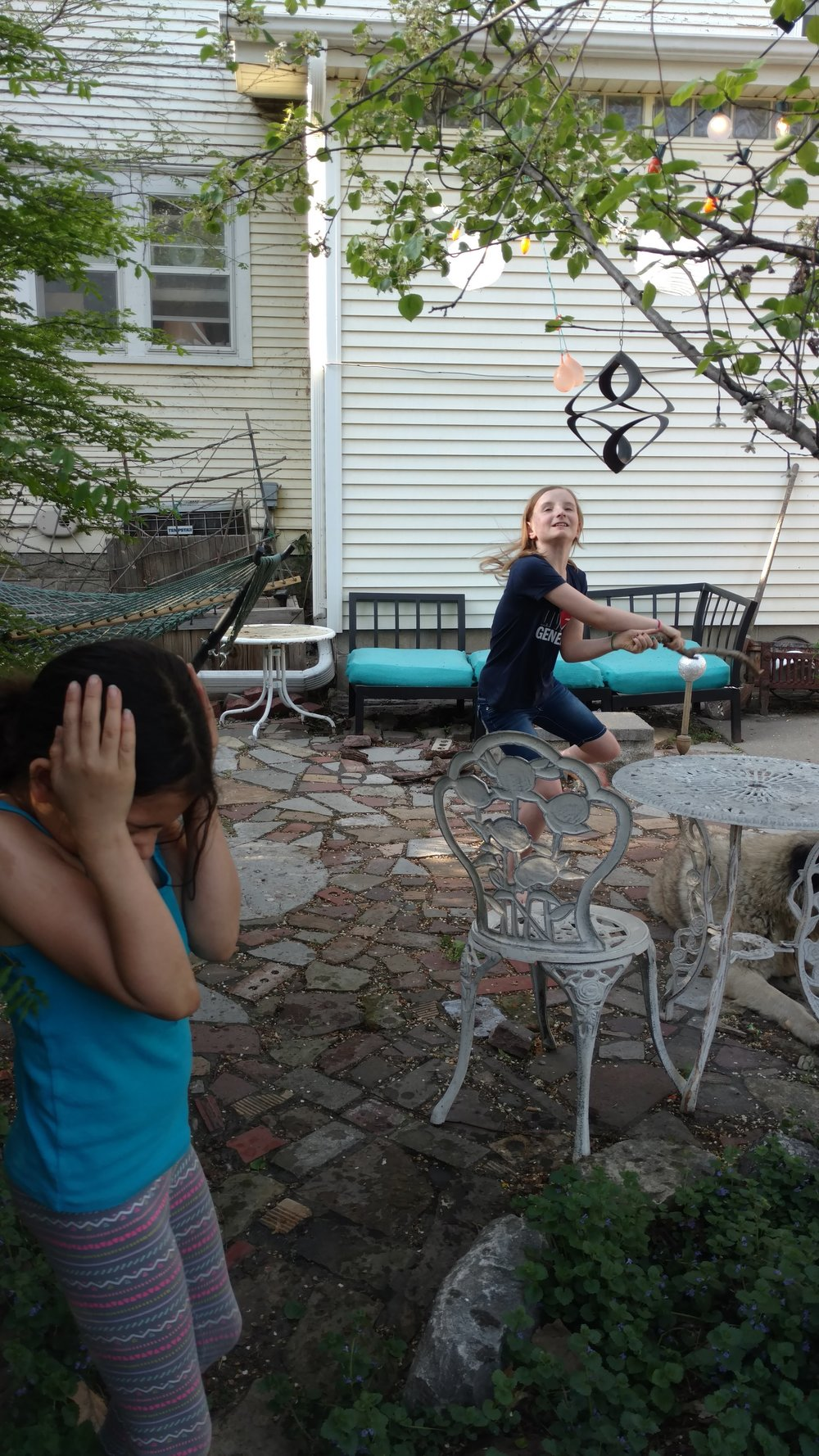 Olivia takes another swing at the water balloon pinata while Ruby ducks.