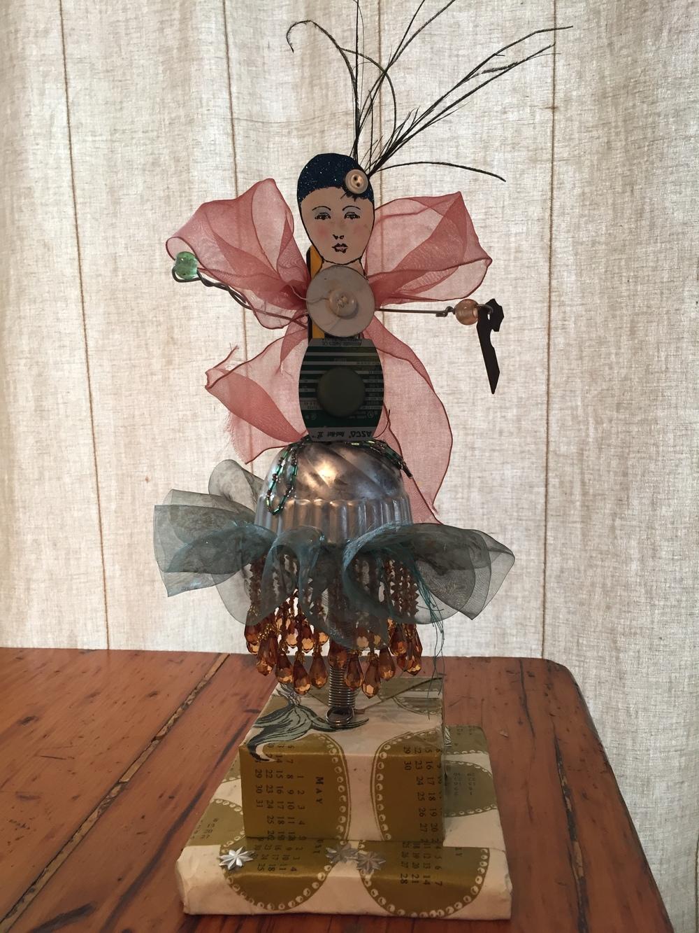 "This figure is made around a screwdriver on a wooden base. The materials include an old jello mold, beads, metal labels, buttons, a wire spring, ribbon, fabric, wire and a paper doll head.  About 12"" tall  $100 plus tax, shipping and handling"