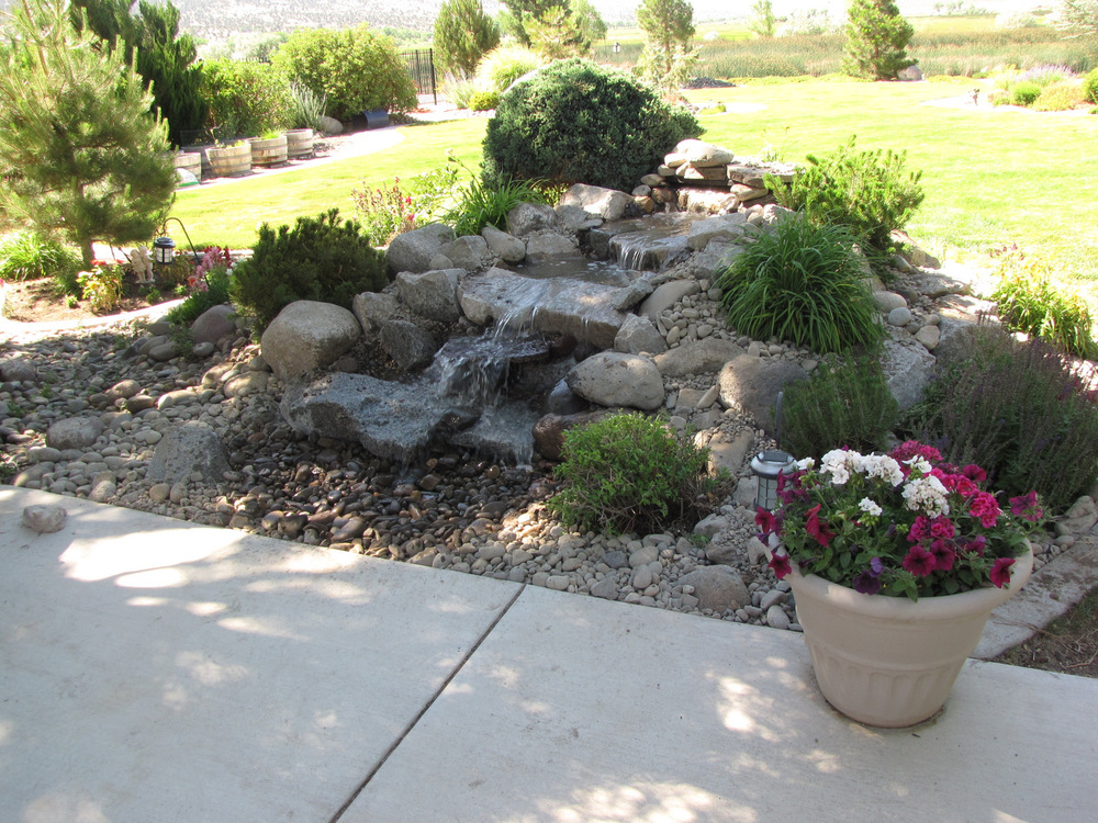 A pondless water feature helps create a peaceful atmosphere near the patio.