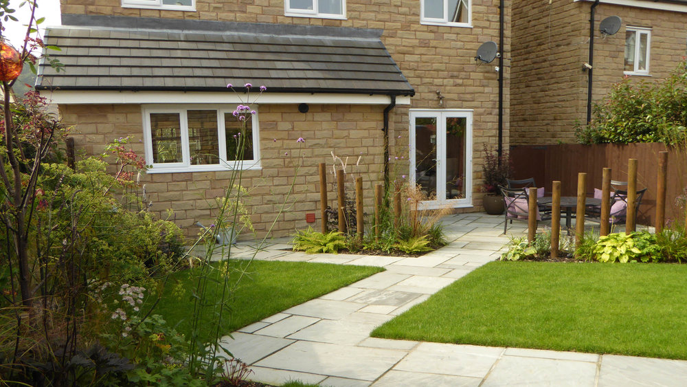 AFTER - New lawn, patio and zig-zig pathway broken by planting beds.