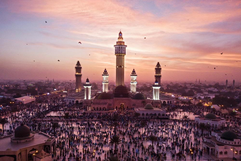 8. November 2017. Fledermäuse schwärmen aus, während sich am Abend des Grand Magal Festes in der Großen Moschee in der heiligen Stadt Touba Tausende von Gläubigen zum Abendgebet versammeln. Die Moschee, in der der Körper von Amadou Bamba begraben ist, wurde am 7. Juni 1963 eingeweiht.