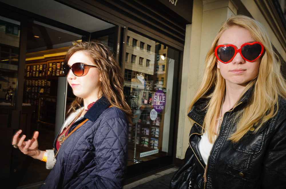 Two young women walking past one with red heart shaped sunglasses