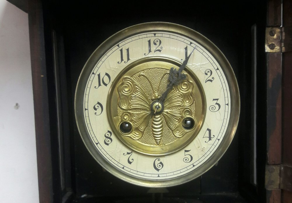 This German wall clock came into my shop for an overhaul . The moth is stamped into a brass center piece .