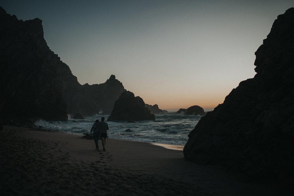 Couple walking at Praia da Ursa during sunset