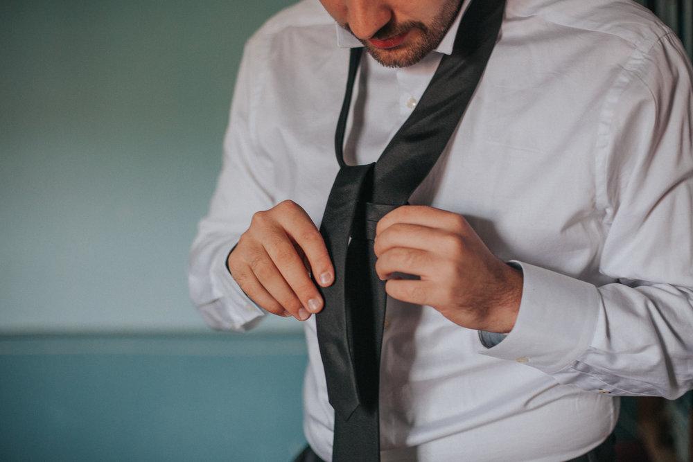Bräutigam bindet seine Krawatte