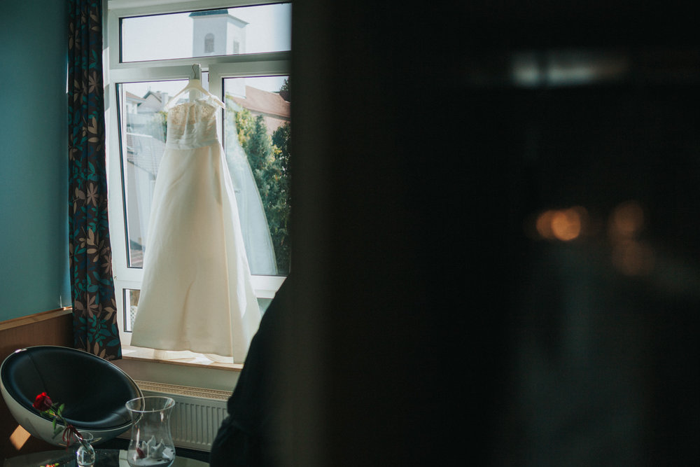 Hochzeitskleid hängt vor einem Fenster
