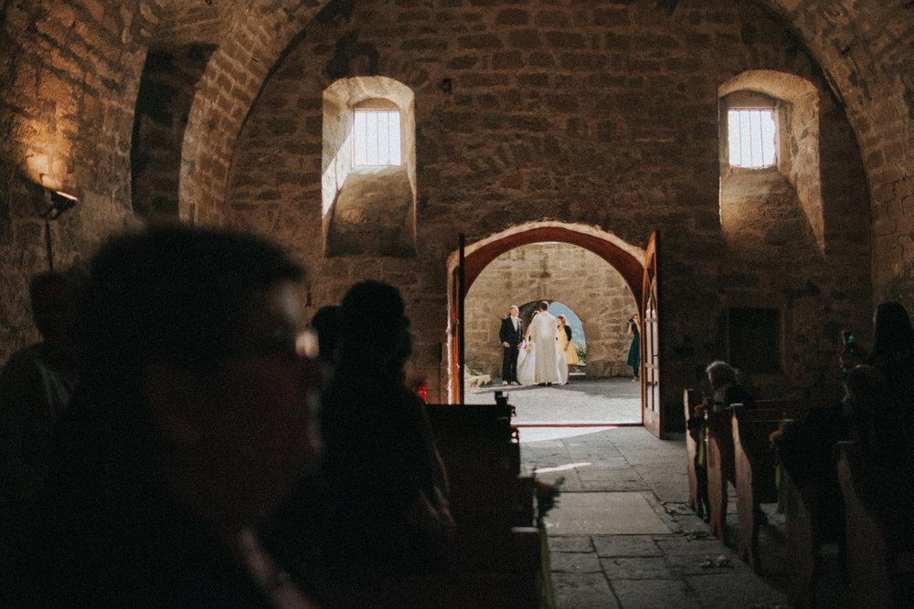 Vor der Traukapelle steht Pfarrer mit Braupaar