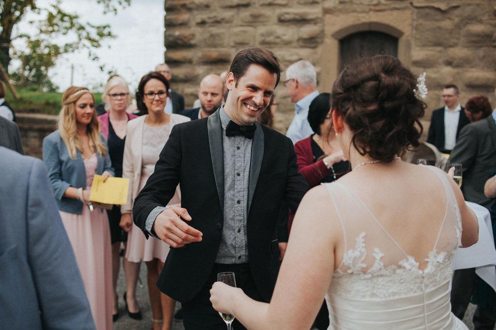 Mann geht lächelnd auf Braut zu