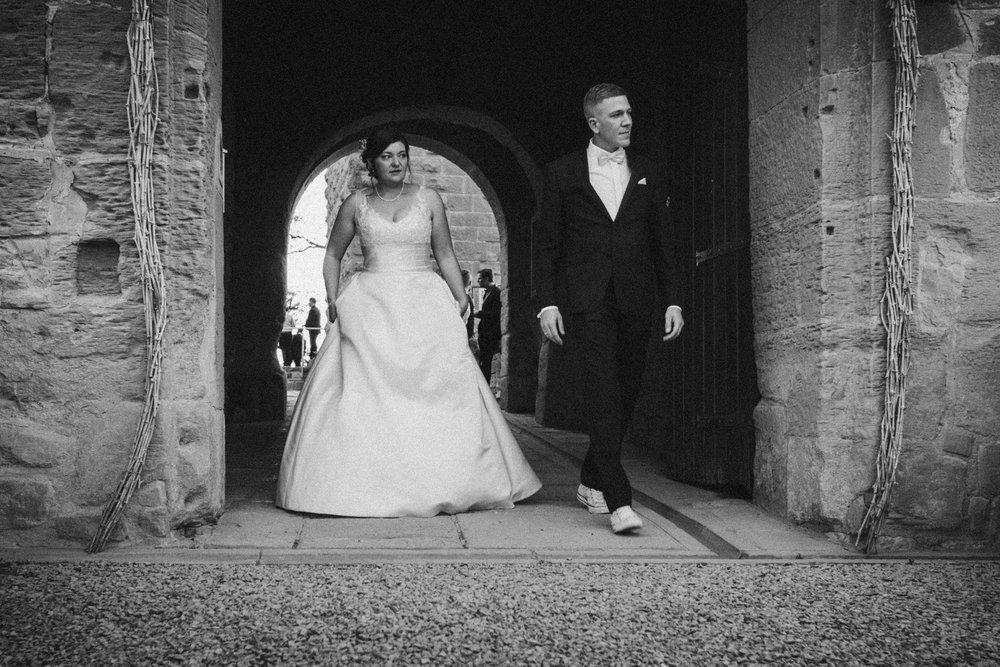 Braut und Bräutigam gehen durch das Tor der Burg Ravensburg