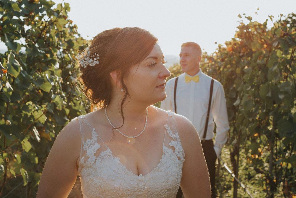 Braut steht vor Bräutigam zwischen Weinreben
