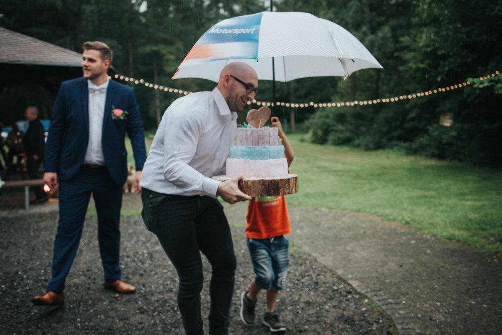 Hochzeitsgast trägt Torte unter Regenschirm