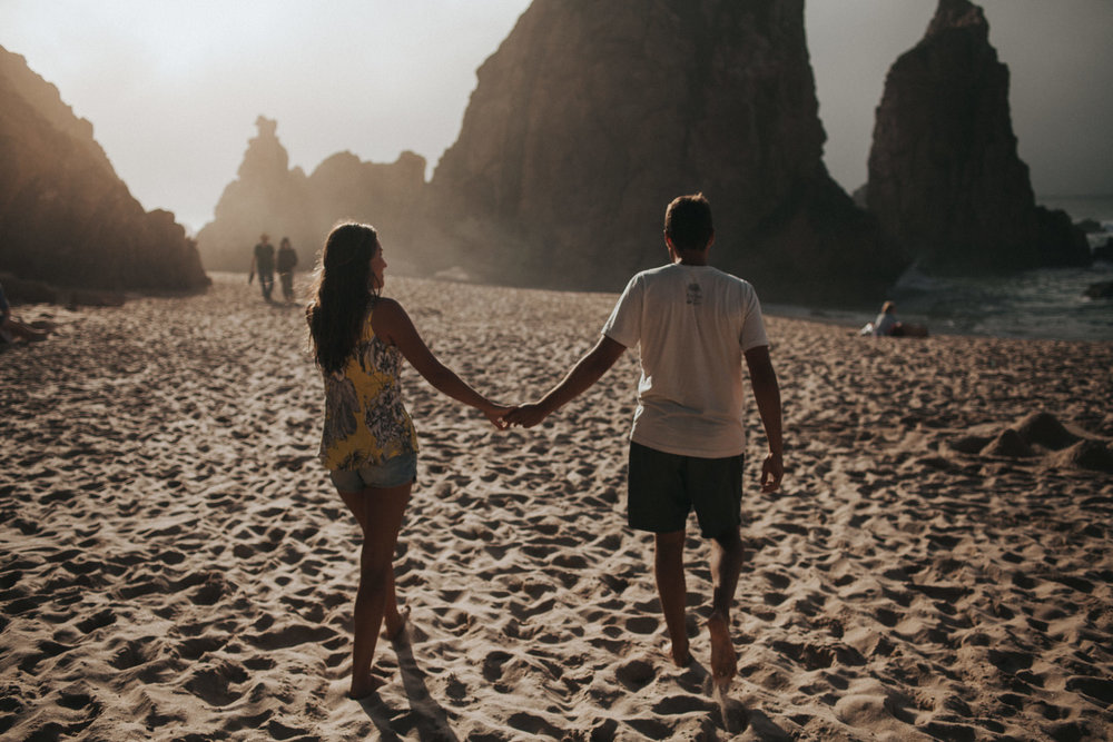 Couple walks hand in hand at the beach