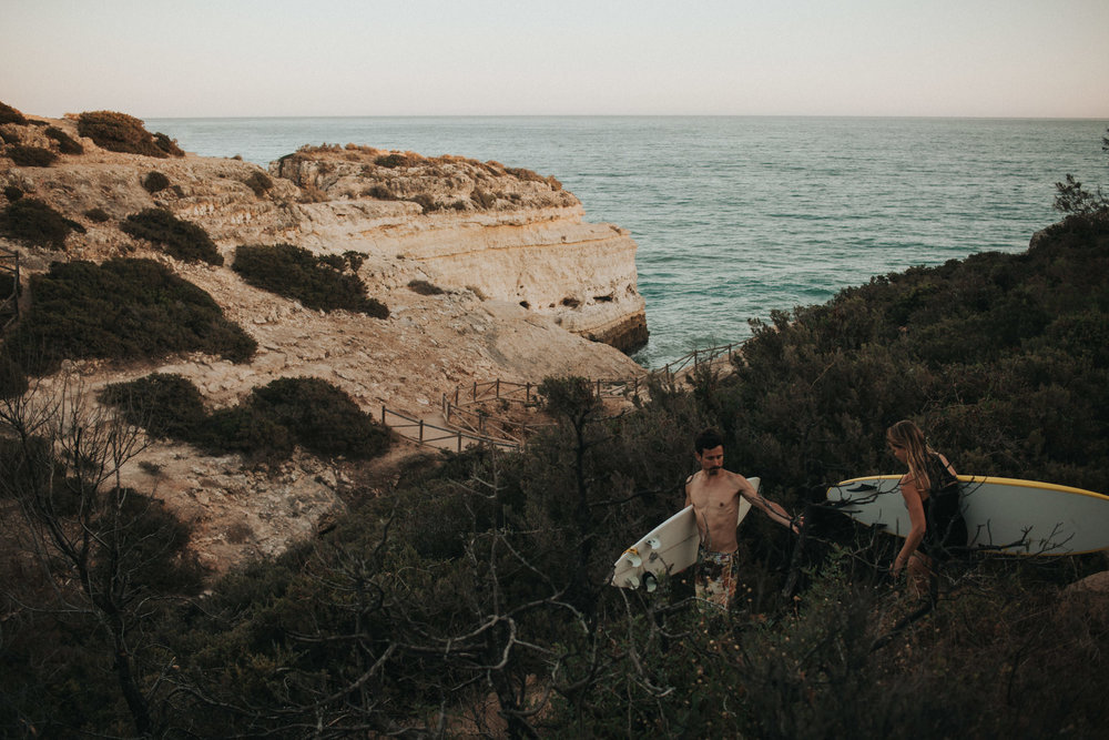 Couple walks with surf boards on the Portuguese cliffs