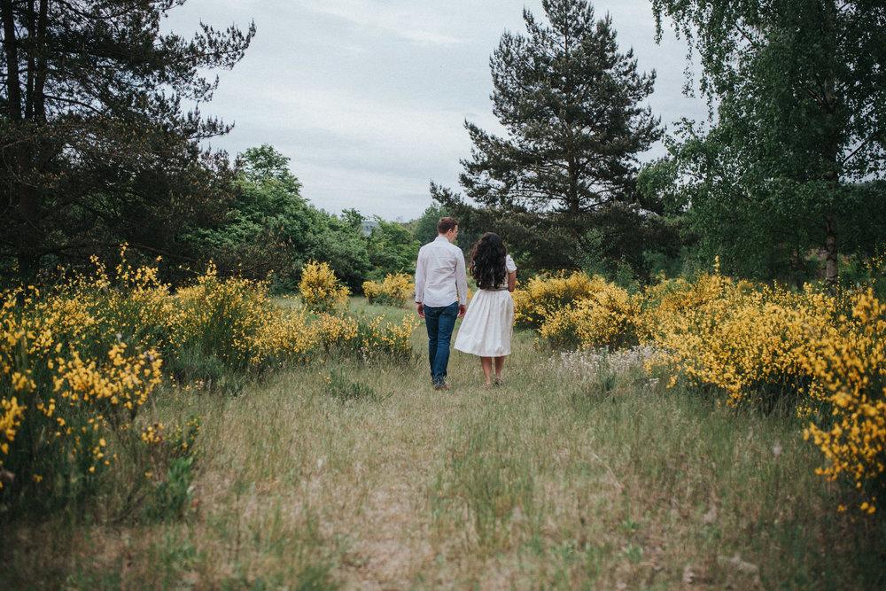 Paar läuft zwischen blühenden Ginsterbüschen