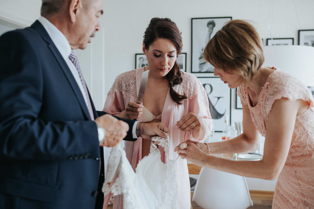 Braut, Vater und Trauzeugin am Kleid