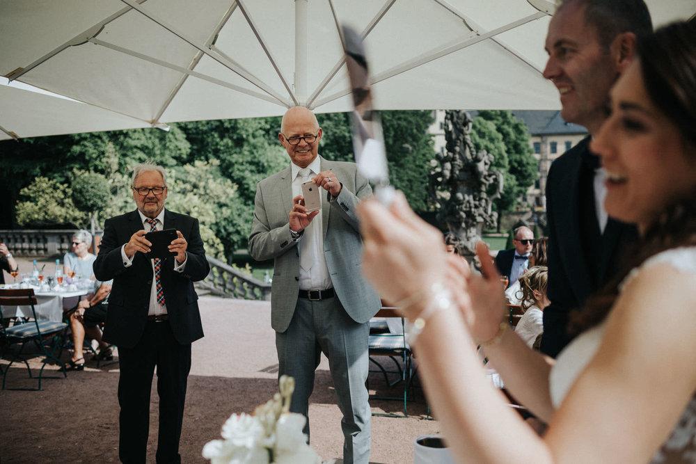 Männer fotografieren den Anschnitt der Hochzeitstorte