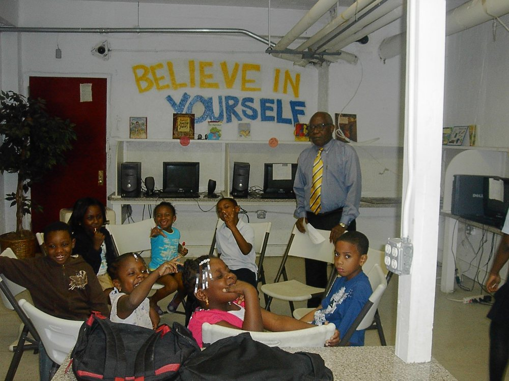 Moses T. T. Jensen counseling children in the community at an after school program.