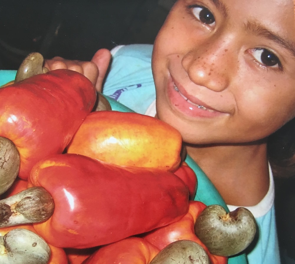 A young El Salvadorian girl carrying cashew fruit. Hustling can start at any age.