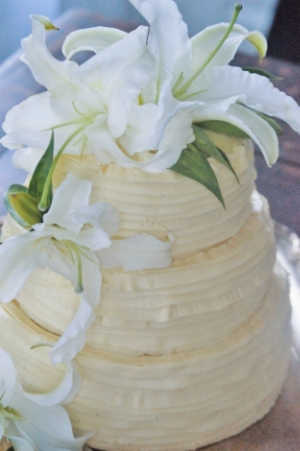Almond Cake, Vanilla Custard Filling, Honey Buttercream Frost  Casually Ruffled Cake with formal white lilies strikes a rustic and elegant balance.