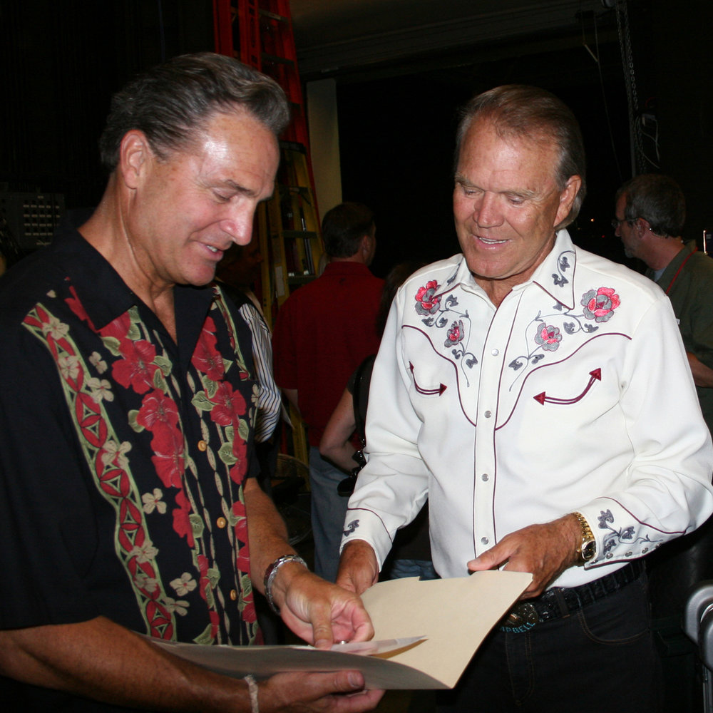 Sharing a laugh with Glen Campbell as they both look at some old photos of themselves together.