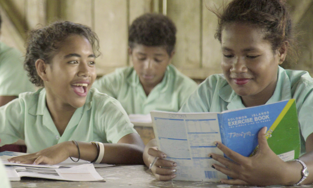 Teenage girls  share a funny  moment during their English lesson at New Place Community High School in Tigoa on Rennel  island. Clean water and girls toilets helps keep teenage girls like them stay in school and opens new doors for them in education