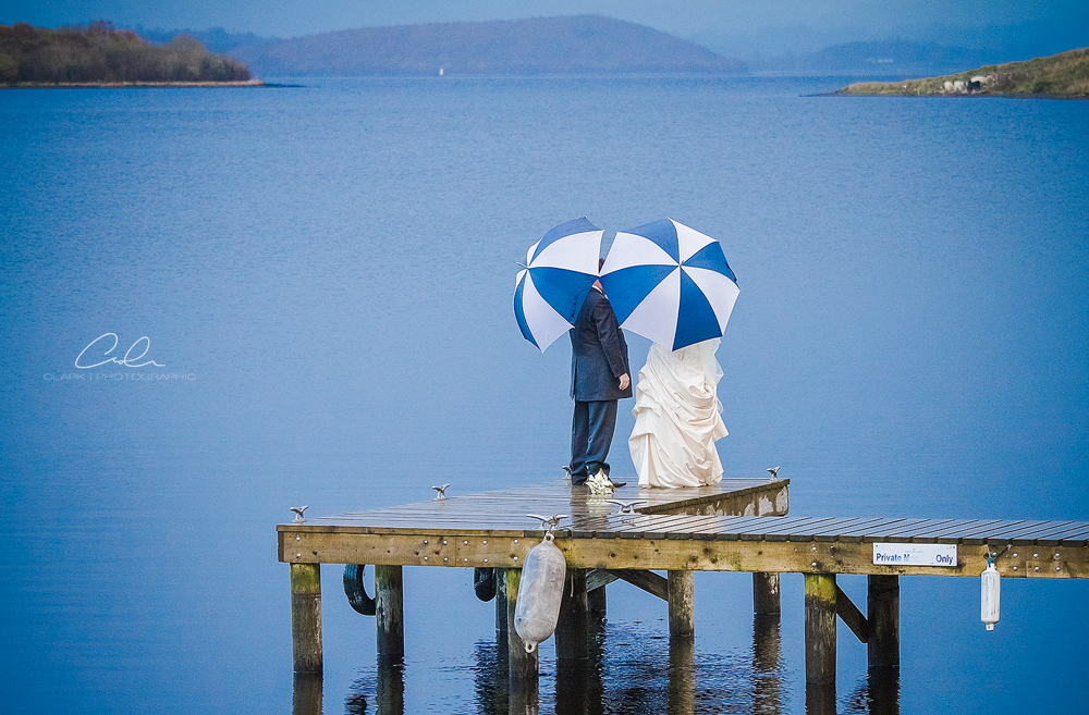 bride and groom umbrellas lusty beg island Derby Wedding Photographer.jpg