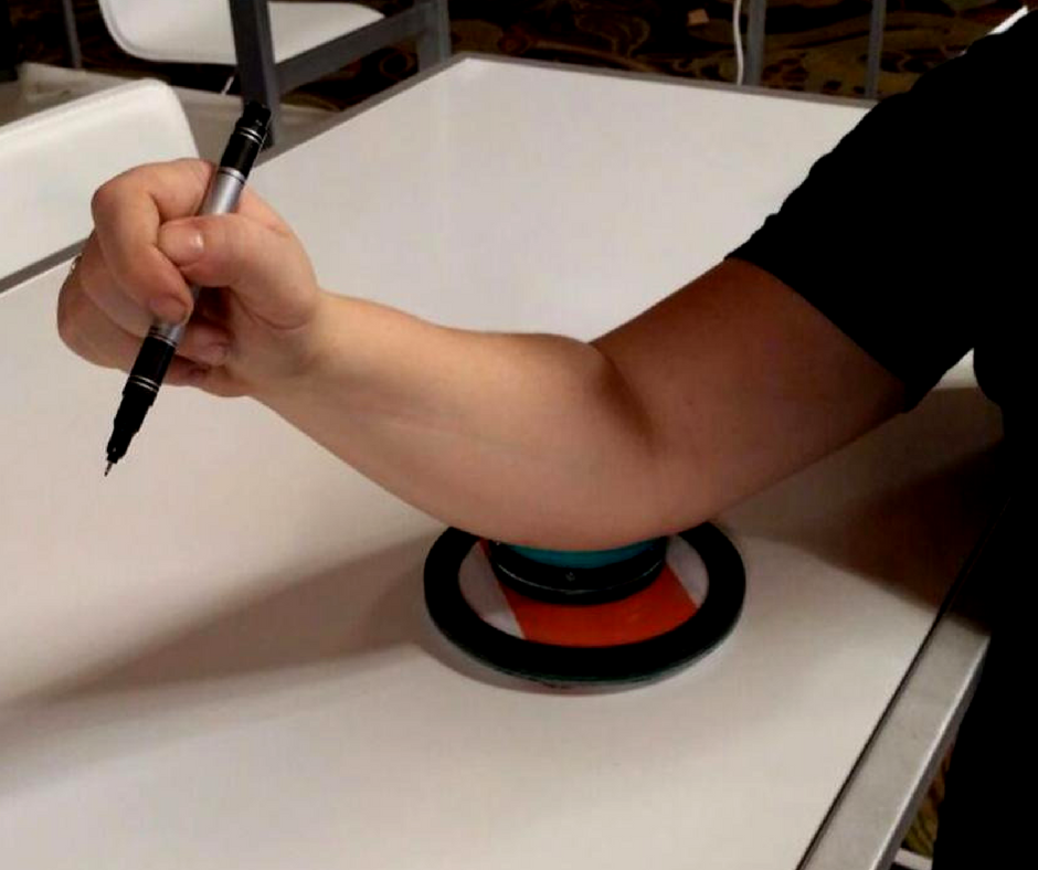Stacy mentioned that Harrison doesn't enjoy writing because of challenges around his fine motor skills. After further analysis, the team noticed that while he has stiffer movement in his wrist, it looked like he just needed a little extra support for his elbow. This small contraption suctions to the table, has a moveable soft disk (held down with magnets) - and will give Harrison the support he needs.
