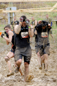 """Elecroshock Therapy: Sprint through a field of live wires — some carrying as much as 10,000 volts of electric shock. Watch out for hay bales and deep mud, or you will face- plant into some electrifying mud. Some Mudders SM try to stealthily wind their way through the wires without getting shocked, while others barrel forward to get through as quickly as possible. Either way, you are guaranteed to get zapped with as much as 10,000 volts of electricity and it does NOT tickle. This is always the last obstacle Mudders must overcome before they cross the finish line. (Toughmudder.com)"""