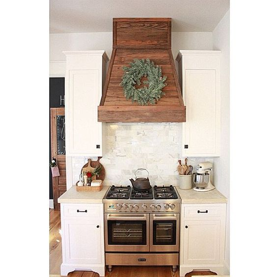 This wooden vent hood is great for contrast against the white cabinets and backsplash. I definitely want a cool hood in my kitchen!   source