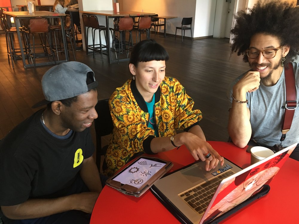 Delson, Slyvia and Seb are sitting at a table in the  Lyric Hammersmith  foyer looking at a laptop