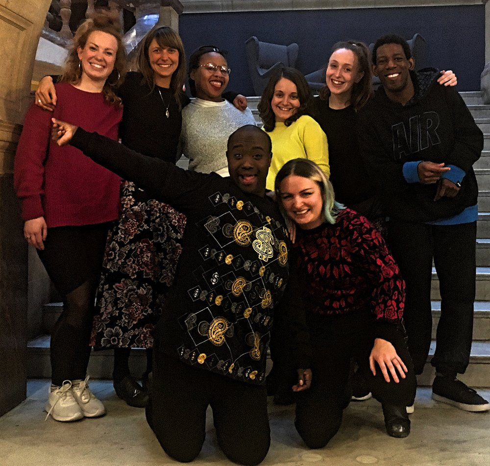 [description] The BLINK Co-Directors are posing with collaborators: writer Caro Horton and Artistic Enablers Cherie Brennan and Tanya Muchanyuka in front of the grand marble steps in the entrance hall at Battersea Arts Centre