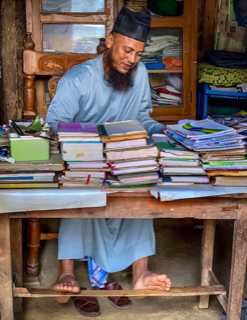 Islamic scholar in the midst of a busy market town. He called his wife and kids out to meet me.