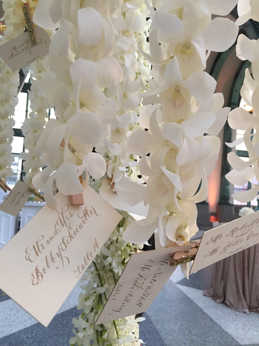 Escort cards hanging from Orchid bloom