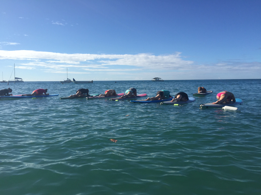 Pigeon pose on a paddle board... I'm in the middle in the grey top/teal bottoms.